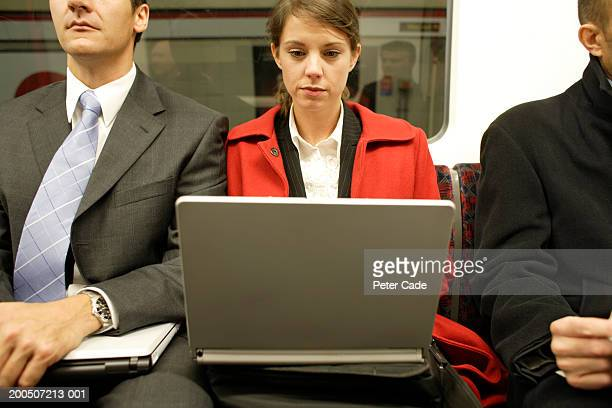 Businessman and woman on underground, woman using laptop