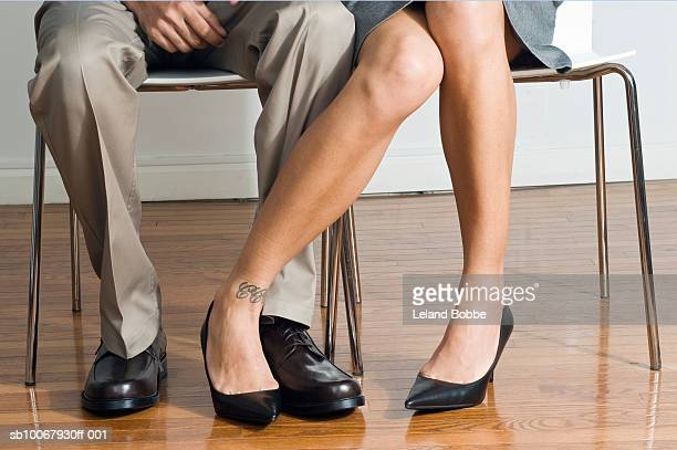 Businessman and woman playing footsie, low section, close-up