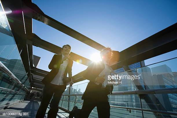 Businessman and woman running across elevated walkway