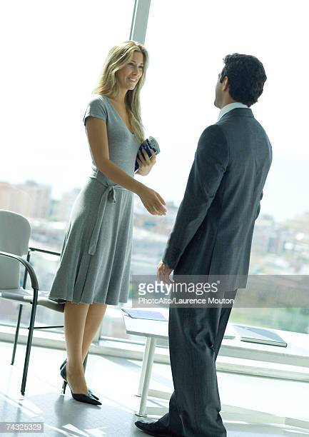 Businessman and woman shaking hands in lobby