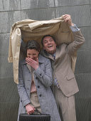 Businessman and woman sheltering under man's coat in rain, laughing