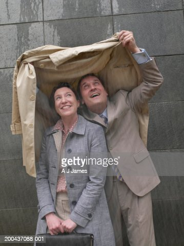 Businessman and woman sheltering under man's coat in rain, smiling