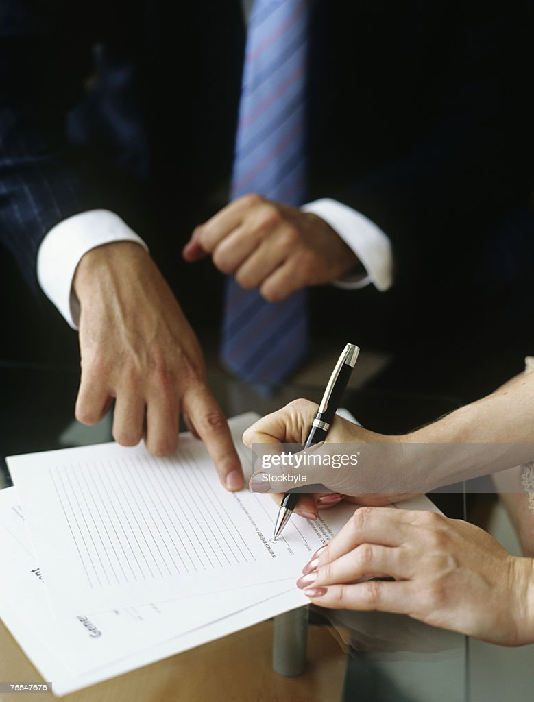 Businessman and woman signing documents,close-up of hands : Stock Photo