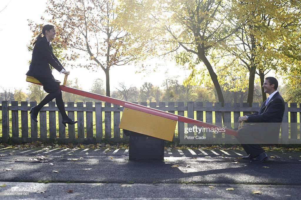Businessman and woman sitting on seesaw, side view : Stock Photo