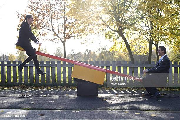 Businessman and woman sitting on seesaw, side view