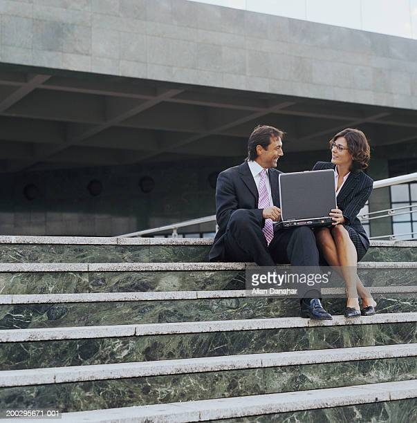 Businessman and woman sitting on steps with laptop, smiling, outdoors