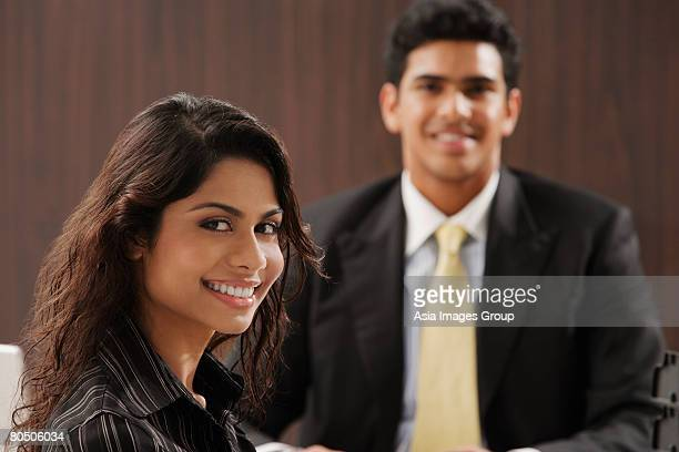Businessman and woman smiling at camera