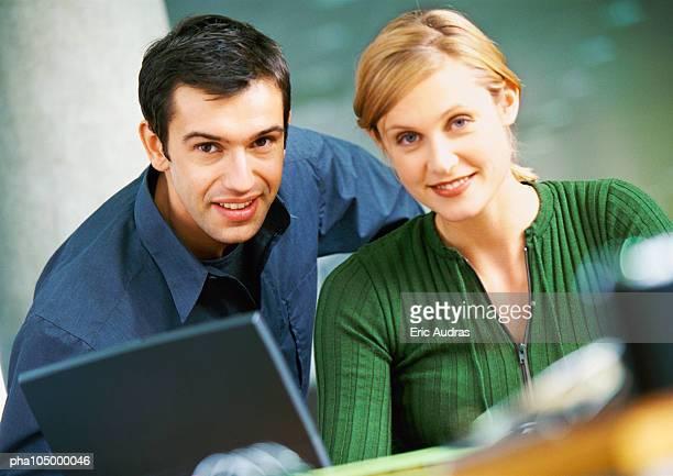 Businessman and woman smiling, portrait