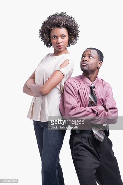 Businessman and woman standing back to back against white background