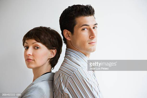 Businessman and woman standing back to back, portrait