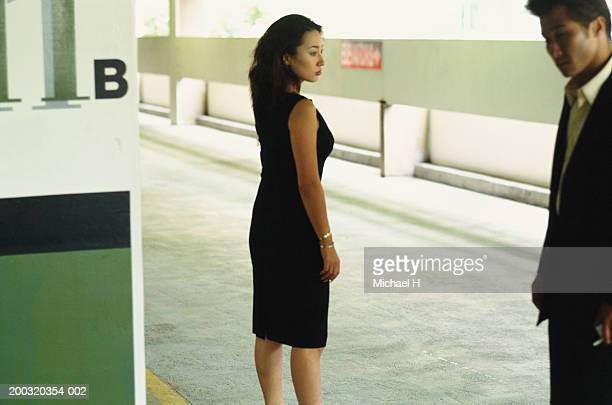 Businessman and woman standing in corridor, focus on woman