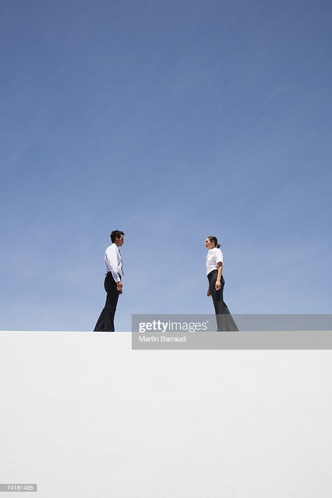 Businessman and woman standing outdoors on wall : Stock Photo
