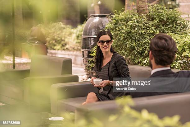 Businessman and woman talking on hotel garden sofa, Dubai, United Arab Emirates