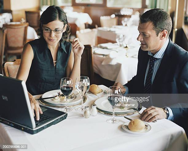 Businessman and woman using laptop at restaurant table