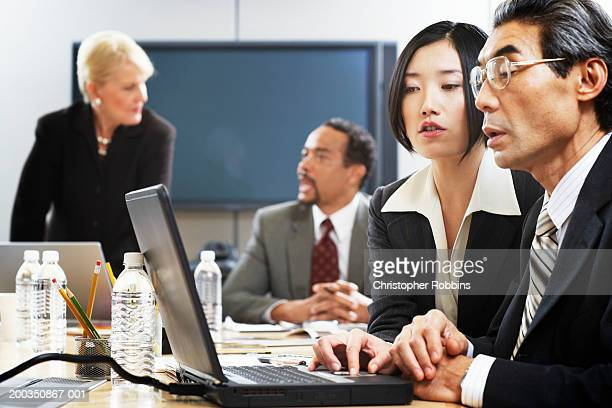 Businessman and woman using laptop computer, side view