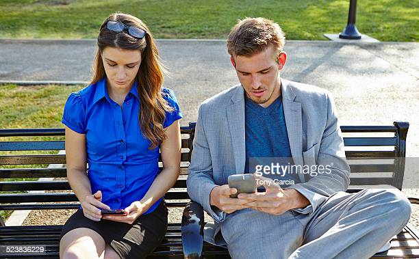 Businessman and woman using smartphone in park