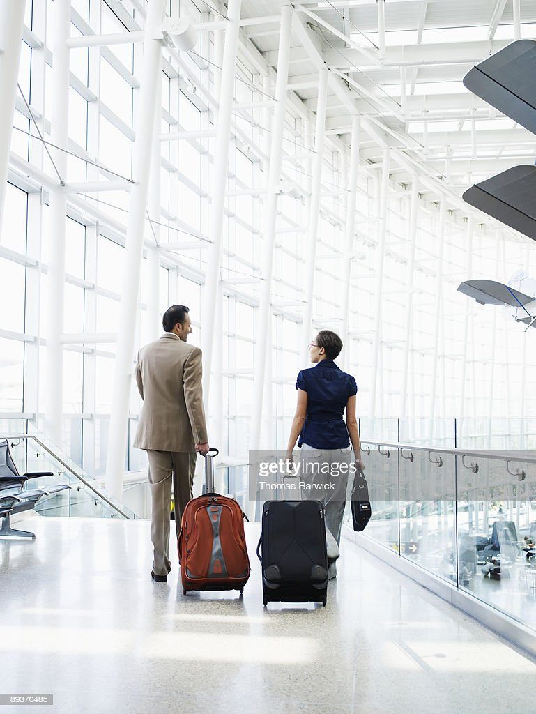 Businessman and woman walking in airport : Stock Photo