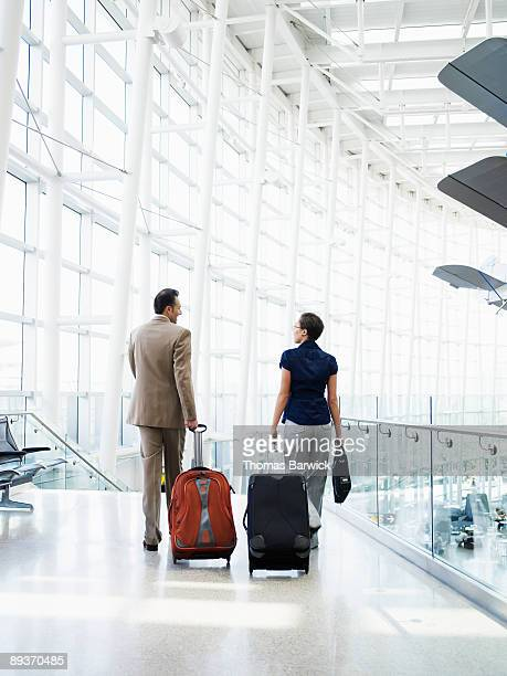 Businessman and woman walking in airport