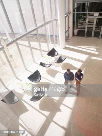 Businessman and woman walking in lobby, elevated view