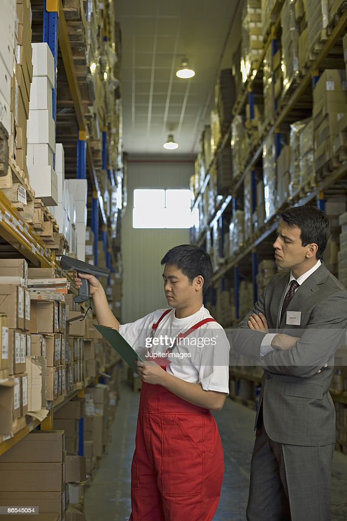 Businessman and worker in warehouse : Stock Photo