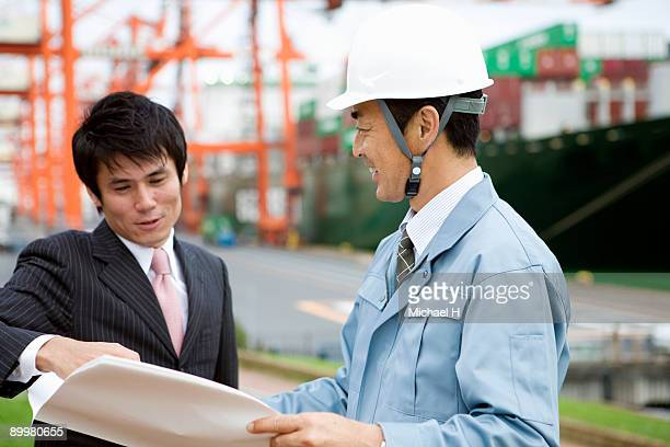 Businessman and worker who sees material and talks