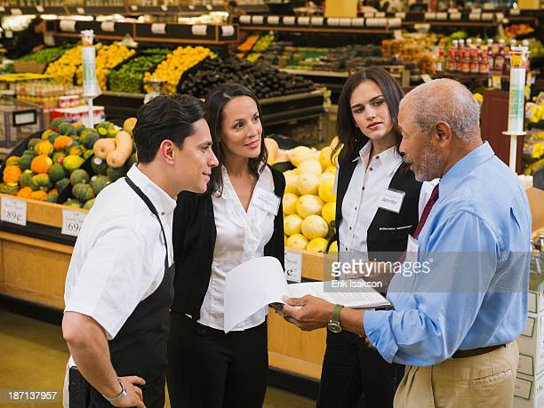 Businessman and workers talking in grocery store