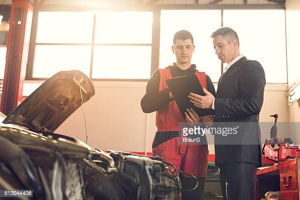 Businessman and young mechanic going through paperwork in repair shop.