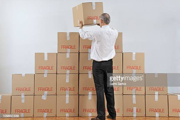 Businessman arranging a boxes pyramid