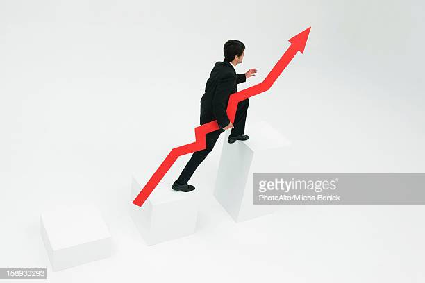 Businessman ascending steps holding arrow pointed upward