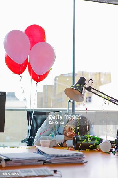 Businessman asleep at desk after party
