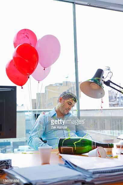 """Empresario en el """"sleep mode"""", en escritorio fiesta posterior"""