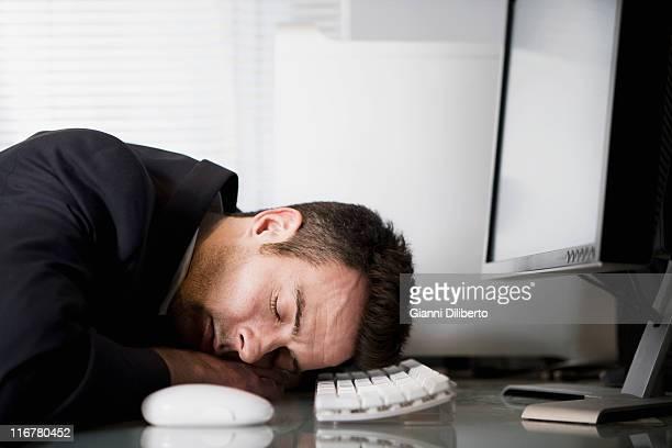 A businessman asleep at his desk