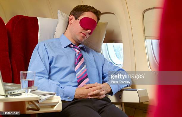 Businessman asleep in first class on plane