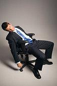 Businessman asleep in office chair