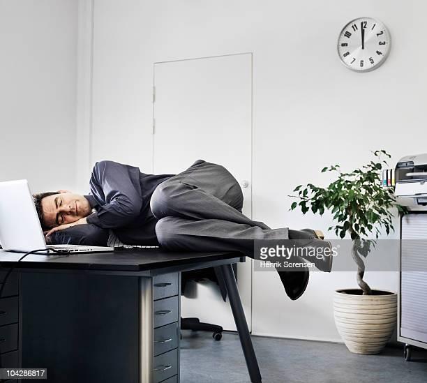 Businessman asleep on his office desk