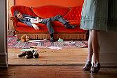 Businessman asleep on sofa in living room, woman standing in doorway