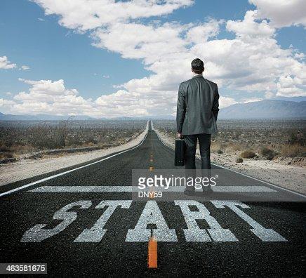 Businessman at a starting line on long desert highway