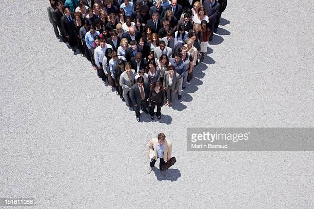 Hombre de negocios en la cúspide de la pirámide formado por multitud