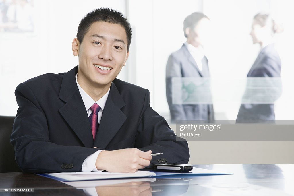 Businessman at conference table, smiling : Stock Photo