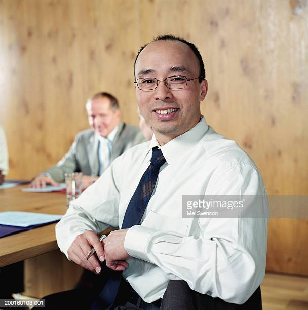 Businessman at conference table, smiling, portrait