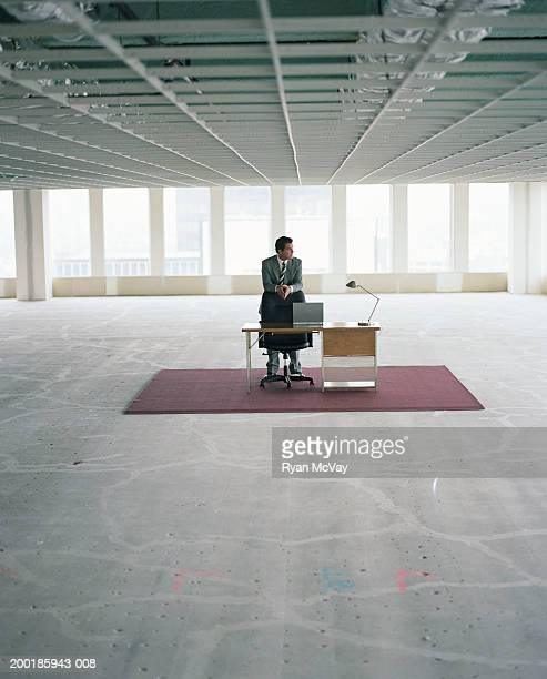 Businessman at desk area in empty office space, looking out window