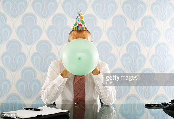 Businessman at Desk Blowing up Party Balloon