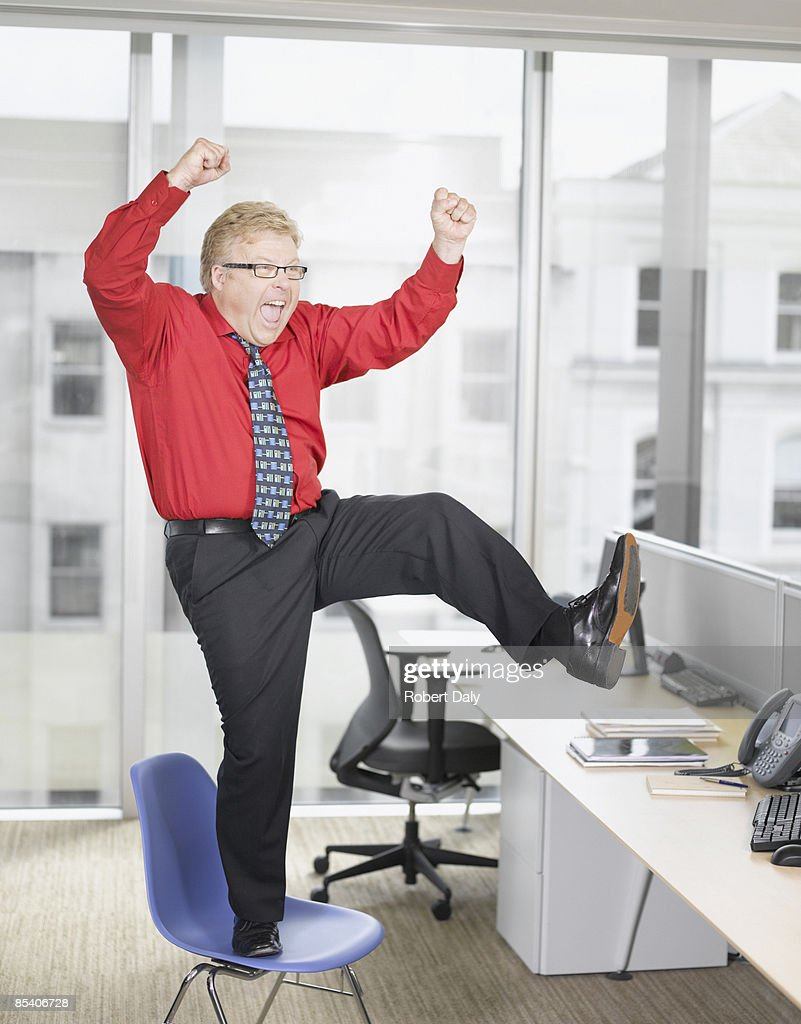Businessman at desk cheering : Stock Photo