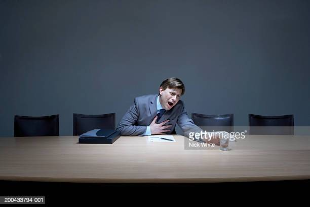 Businessman at desk, clutching heart while reaching for glass of water