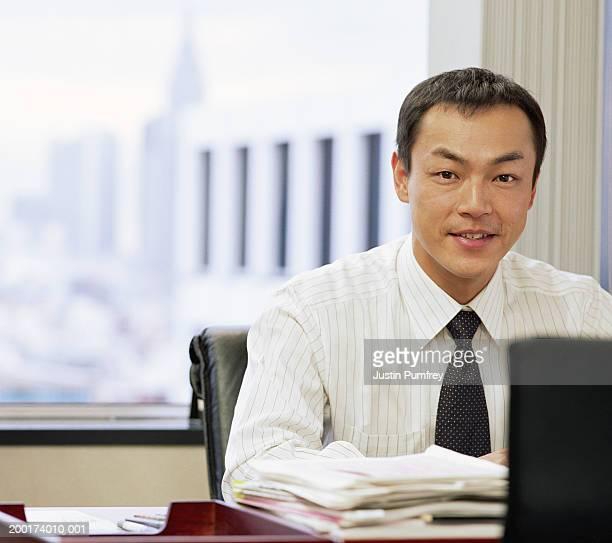 Businessman at desk, smiling, portrait