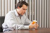 Businessman at desk studying pill bottles