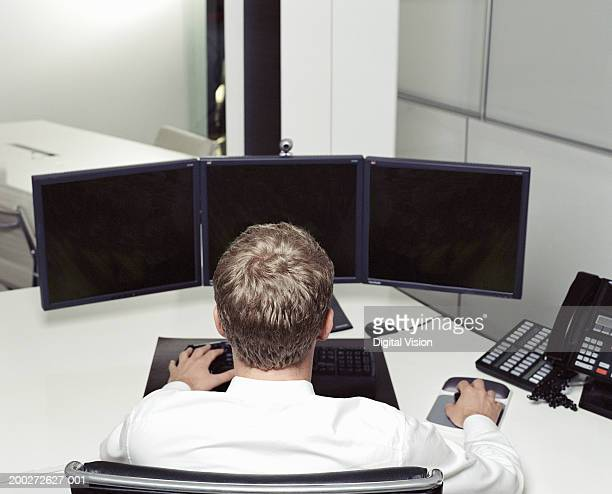 Businessman at desk using computer with multiple screens, rear view