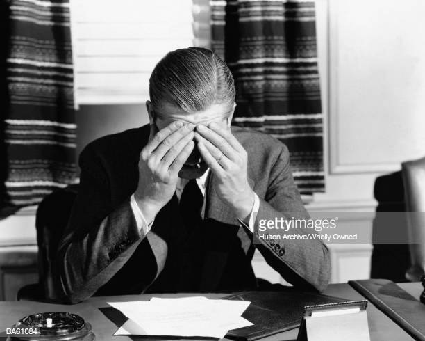 Businessman at desk with hands on head (B&W)