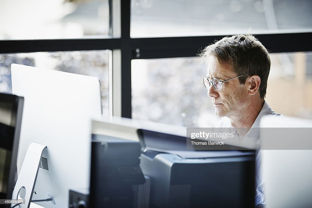 Businessman at desk working on computer : Stock Photo