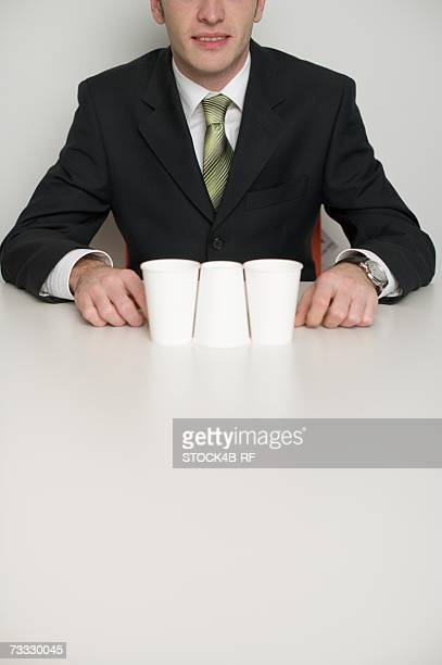Businessman at desktop, in foreground three cups